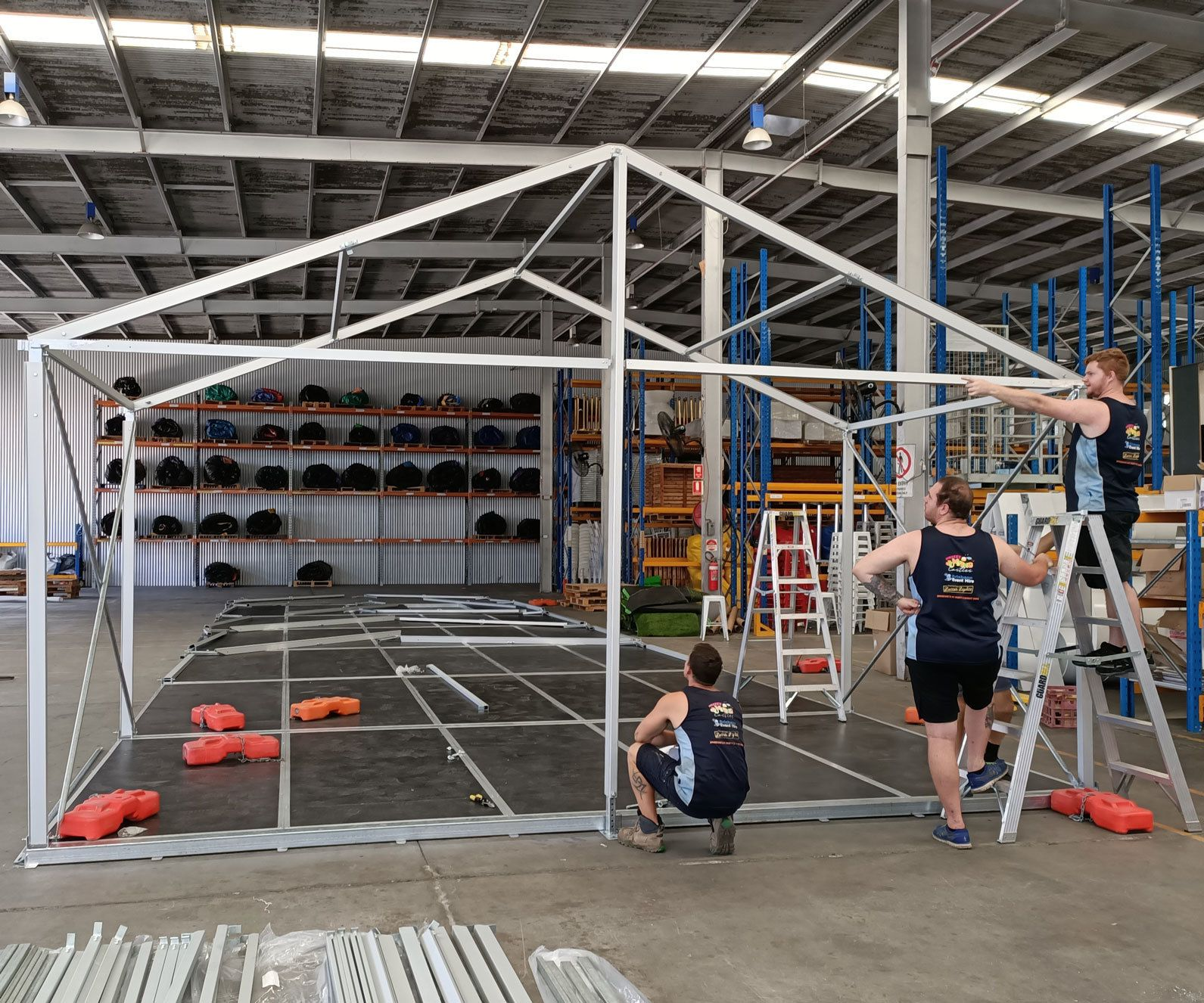Warehouse Workers Assembling A Party Marquee
